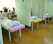 明るい院内、ピンクとイエローのベッド