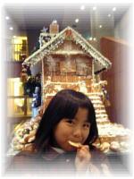 お菓子の家の前でせんべいを食べるSAYAKA