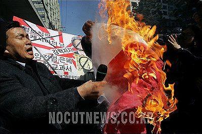 日本大使館前で日の丸を燃やす朝鮮人。