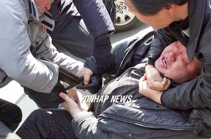 指を切ろうとして警察に止められる朝鮮人。